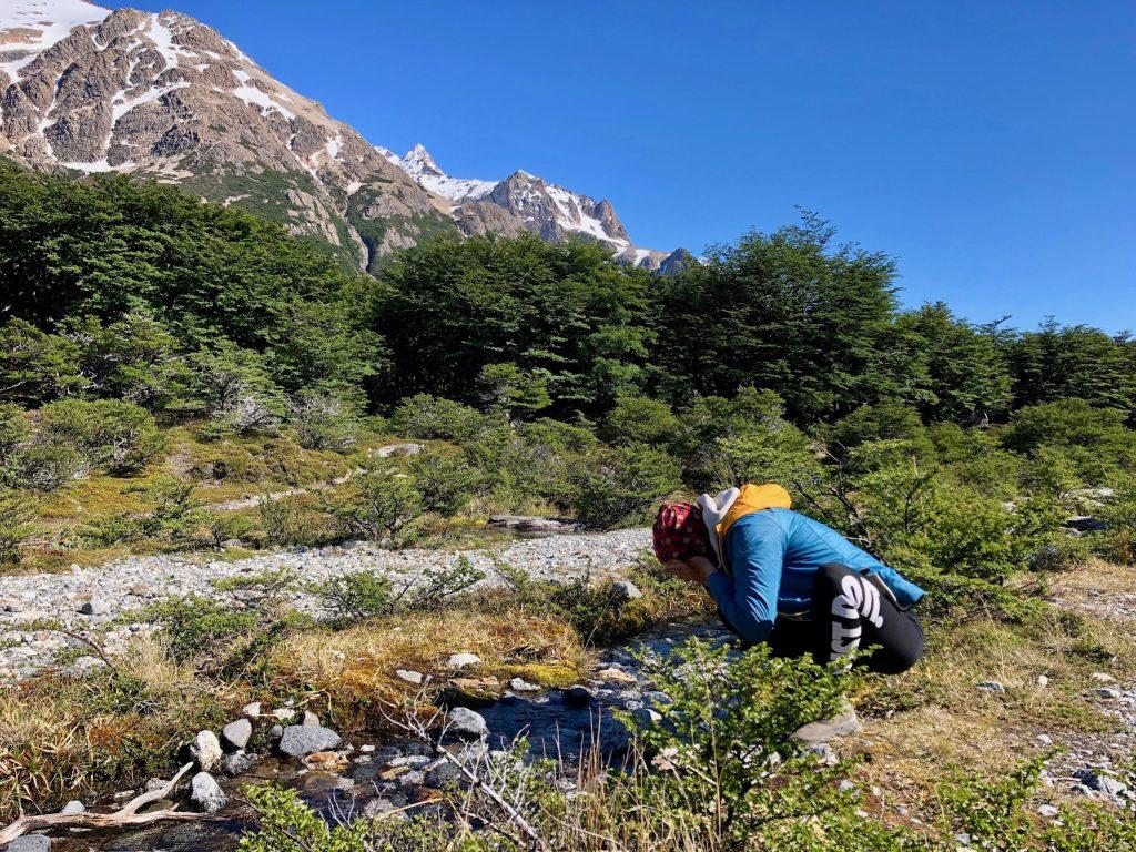 Bachlauf mit Gebirgsmassiv und grünen Sträuchern, an denen sich Charlotte vom Rausgier-Blog wäscht.