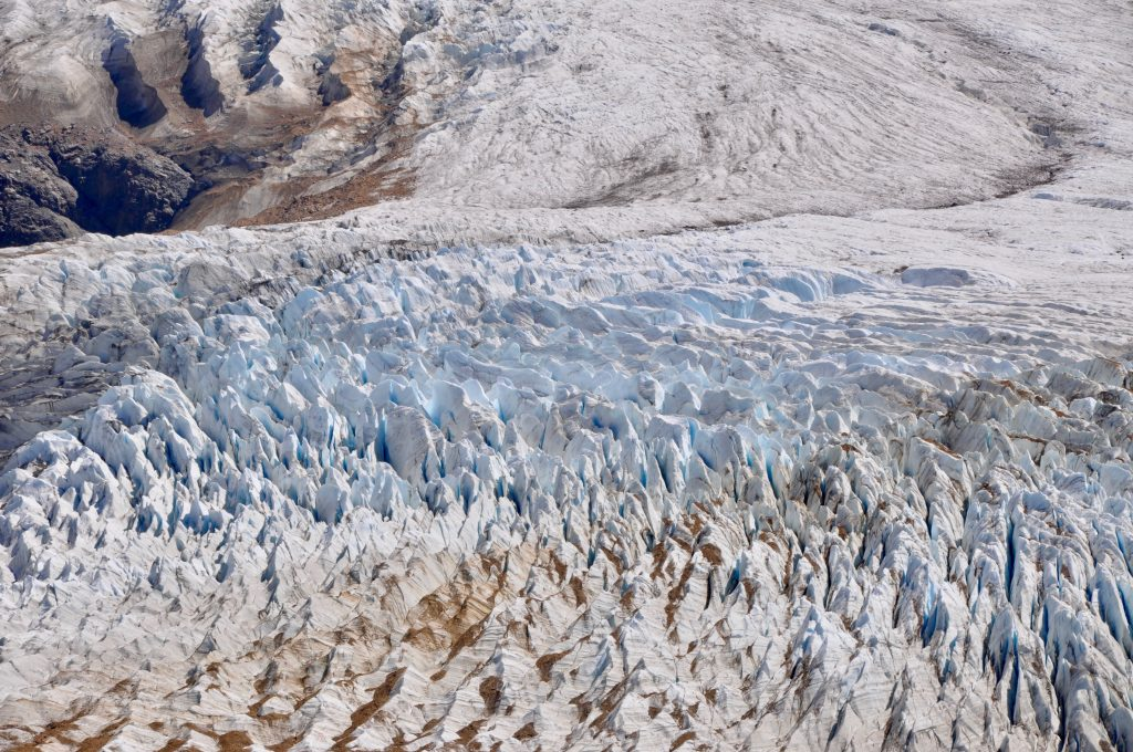 Nahaufnahme des Gletscher Grande mit feinen, blauen Gletscherspalten und aufgelagertem, braunem Sediment.