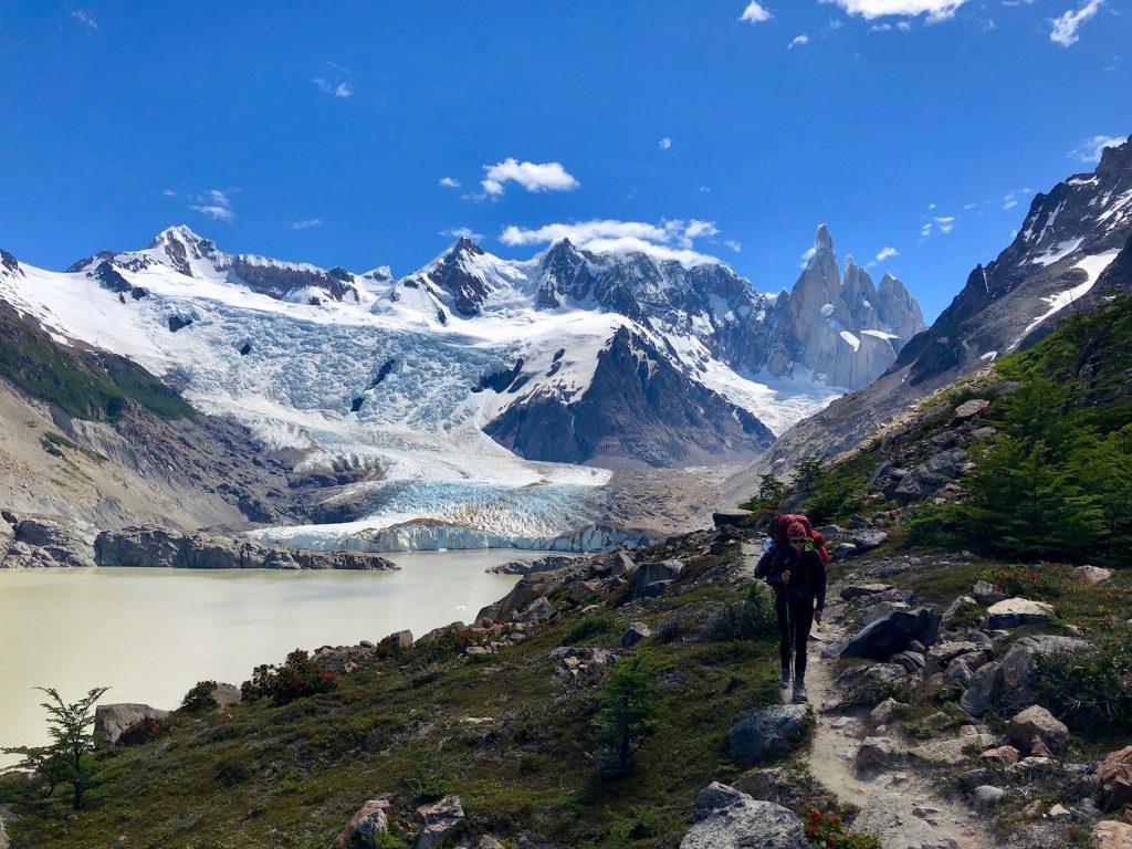 Charlotte vom Blog Rausgier mit Trekkingrucksack vor Gebirgspanorama mit Cerro Torre, Laguna Torre und Gletscher Grande.
