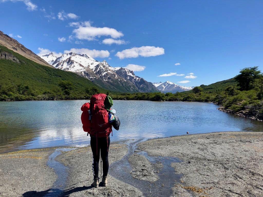 Charlotte vom Blog Rausgier steht mit einem großen, roten Trekkingrucksack an einem See vor Gebirgspanorama in Patagonien.