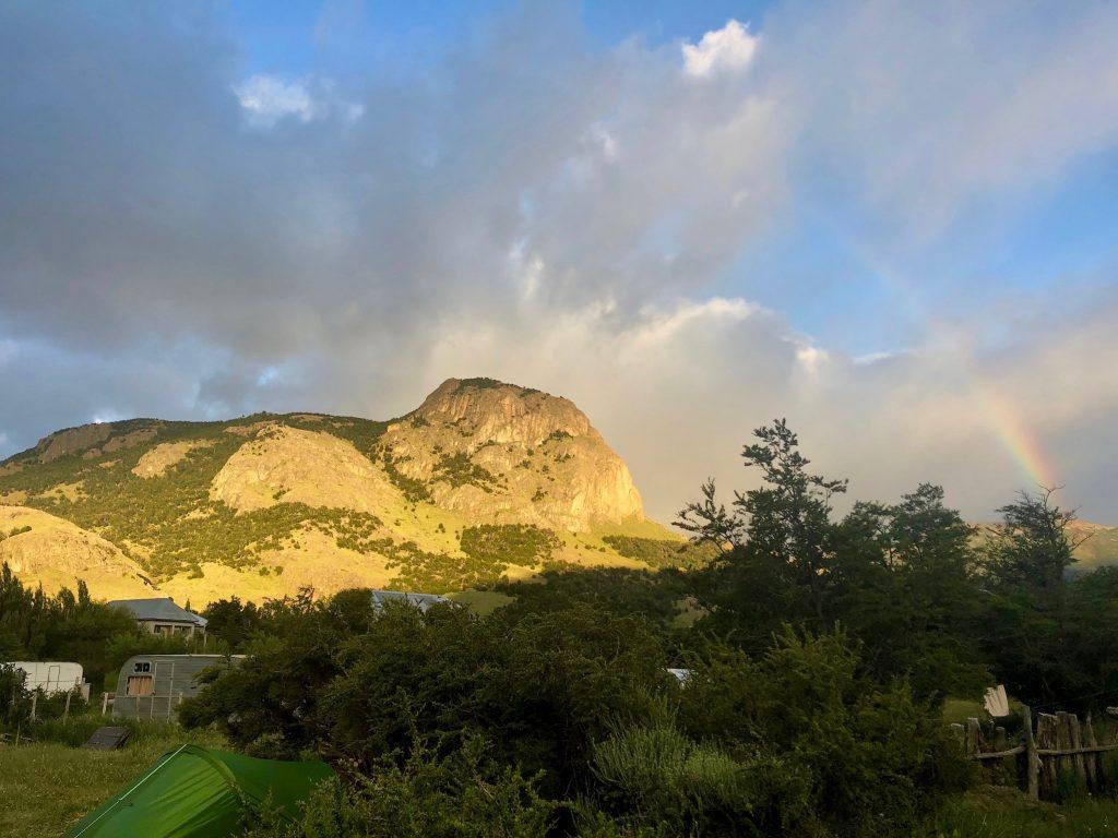 Zeltplatz El Relincho in El Chaltén in der Abendsonne mit Regenbogen am Himmel.