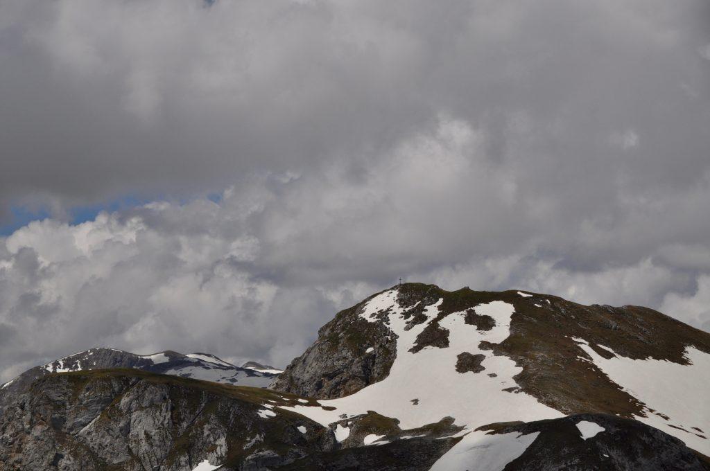 Aussicht auf den Eiskogel mit Gipfelkreuz über einen schneebdeckten Hang.