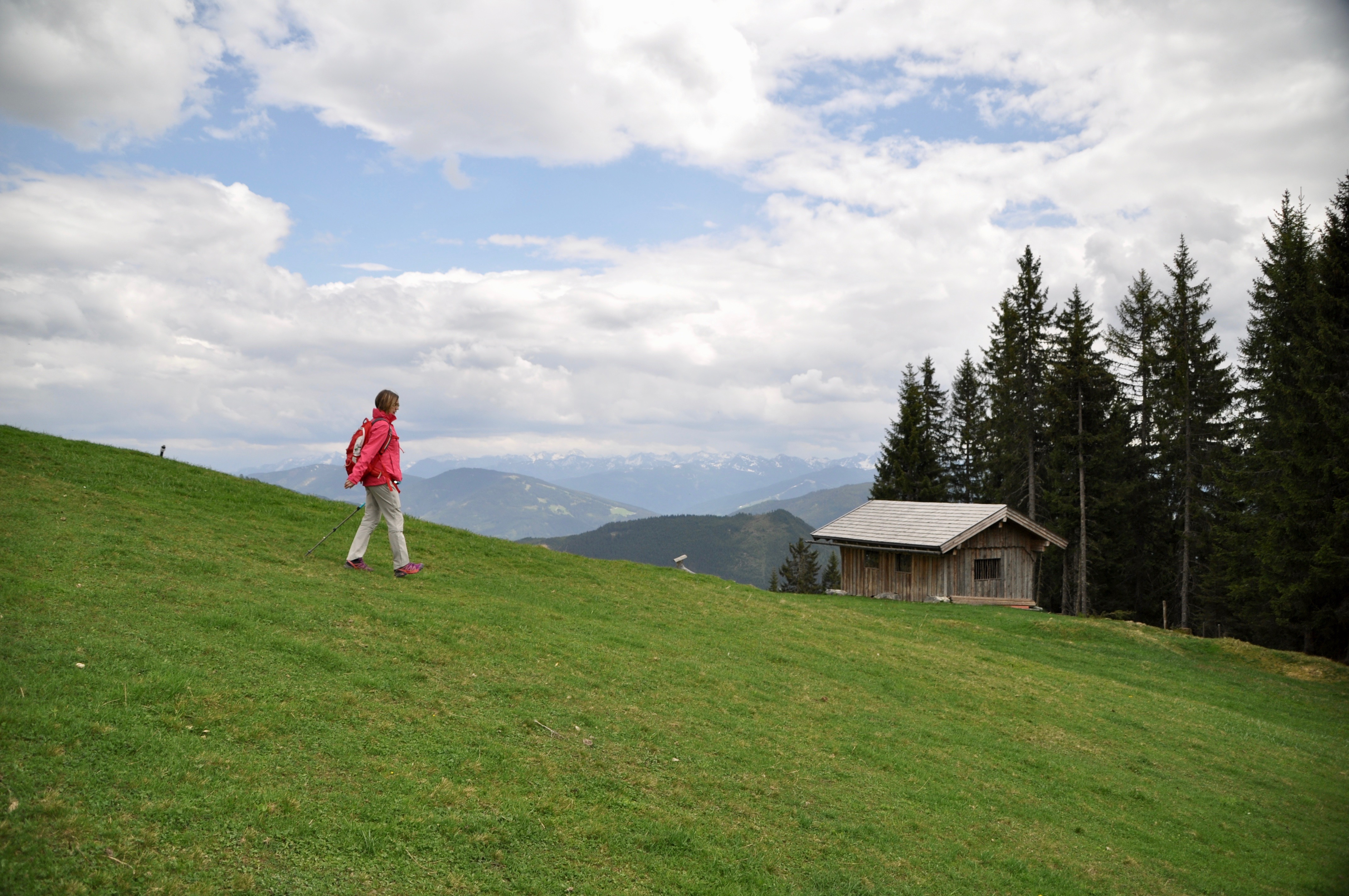 Eine Frau wandert vor einer Alpenkulisse als Teil einer Wandergruppe eine grüne Wiese hinab.