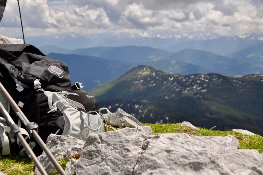 Der Osprey Talon Wanderrucksack liegt am Fuß des Gipfelkreuzes des Tauernkogels. Dazu die Aussicht auf das Tennengebirge mit schneebedeckten Gipfeln in der Ferne.