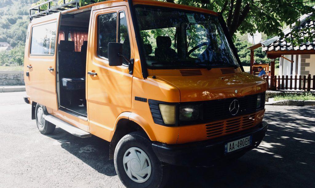 Ein orange-gelber Mercedes-Bus vor grünem Berg und Häuschen bringt Trekker zum Peaks of the Balkans.