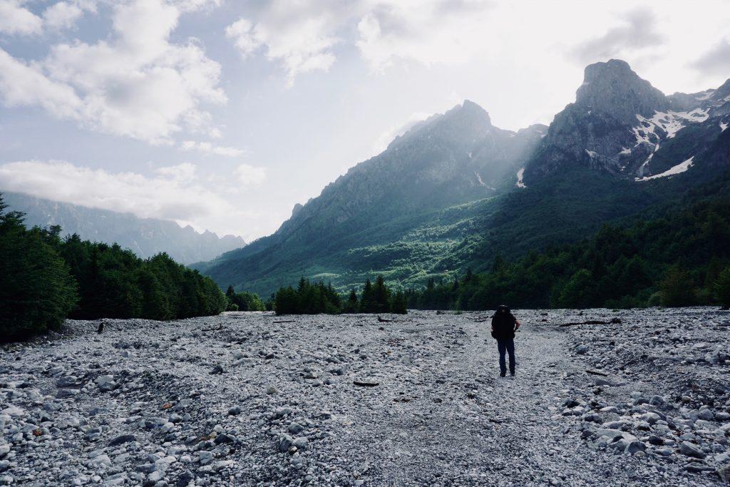Ein Mensch mit Trekkingrucksack geht auf einem Geröllfeld entlang, an dessen Seiten sich ein Bergmassiv hochzieht, durch das Licht bricht.