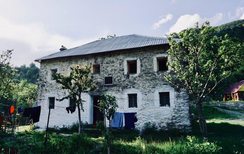 Ein Steinhaus inmitten grüner Bäume am Peaks of the Balkans.