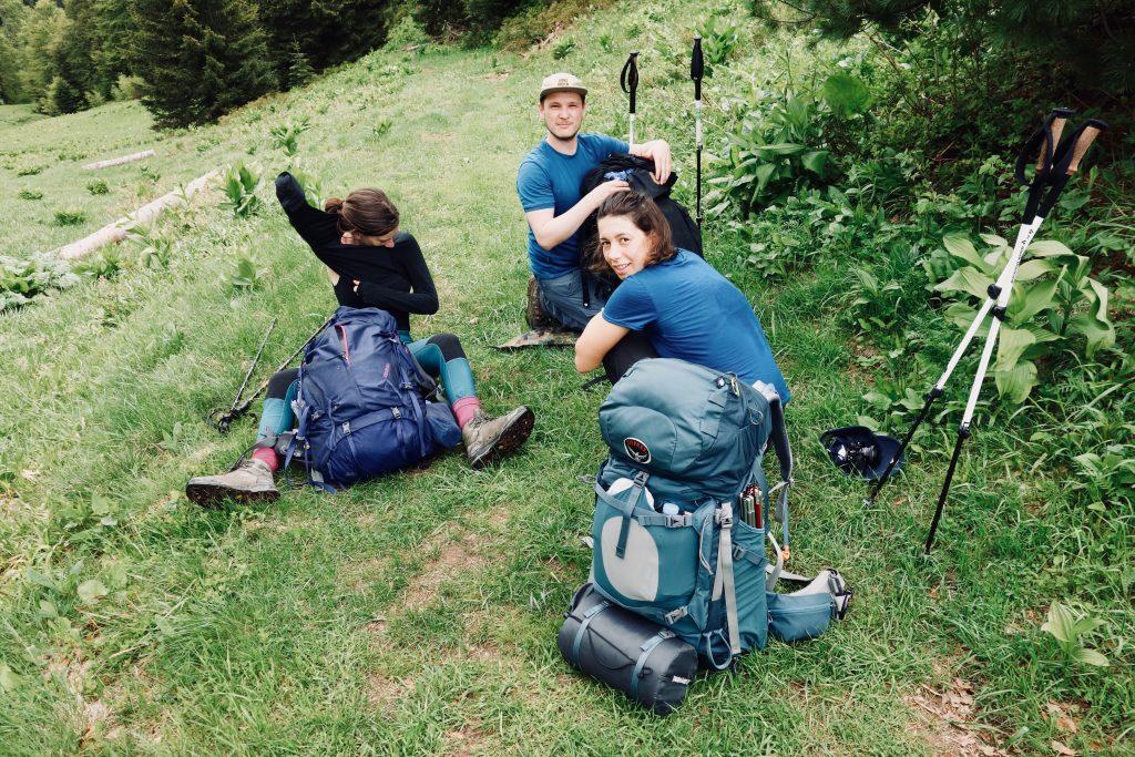 Drei Trekkingreisende sitzen mit ihren Rucksäcken auf grüner Wiese.