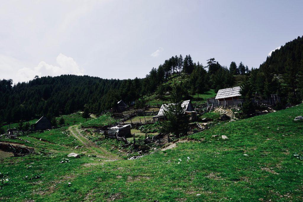 Eine Holzhütte auf grüner, gebirgiger Wiese.