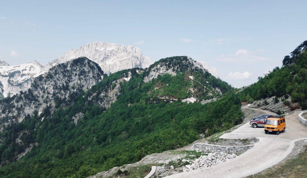 Ein Parkplatz mit drei parkenden Autos vor Gebirgskulisse mit Grün kurz vorm Einstieg in den Peaks of the Balkans.