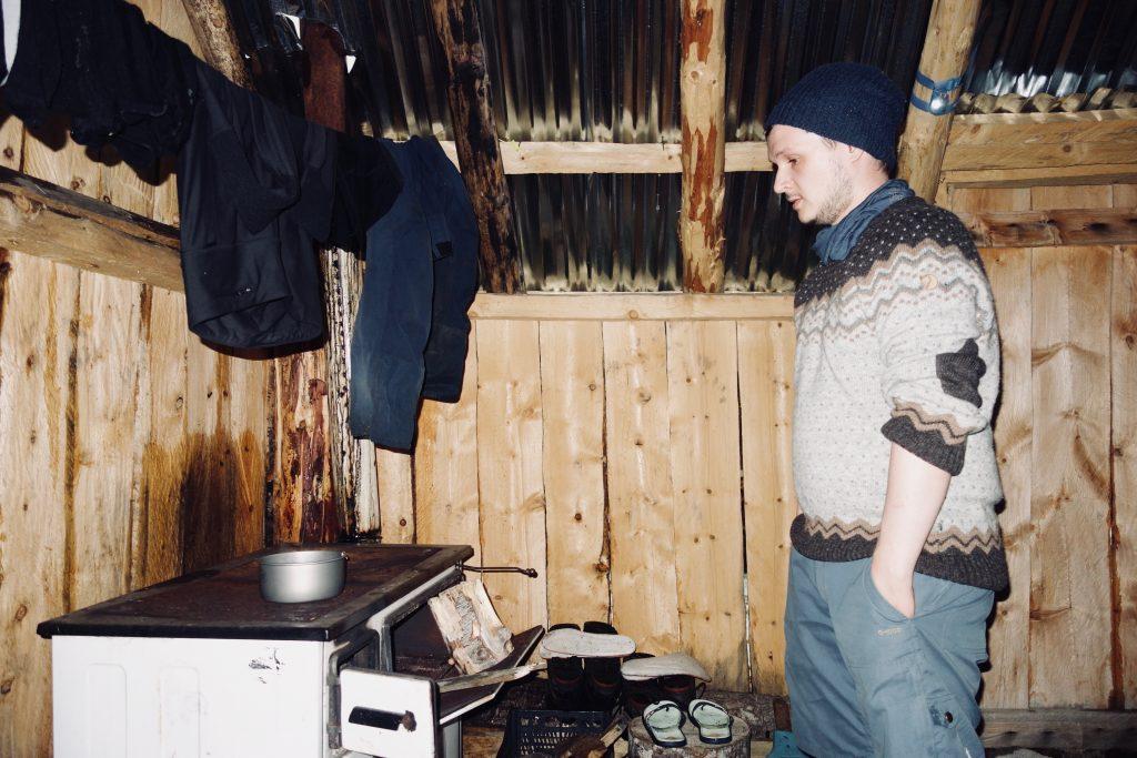 Ein Mann steht im Wollpulli an einem Ofen in einer Holzhütte.