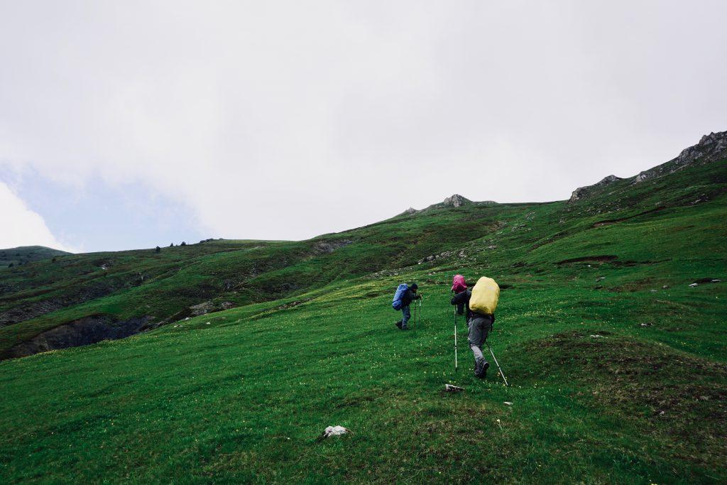 Trekker mit Rucksäcken, die in bunte Regenhüllen gepackt sind, auf dem Peaks of the Balkans.