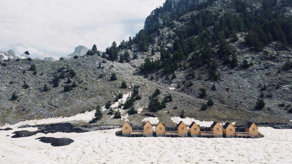 Holzhäuschen auf Schnee vor einer Gebirgskulisse.
