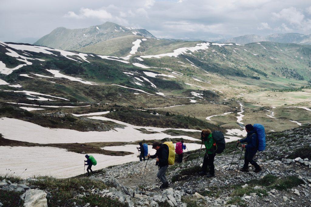 Abstieg aus dem Schneefeld ins grünere Tal auf dem Peaks of the Balkans.