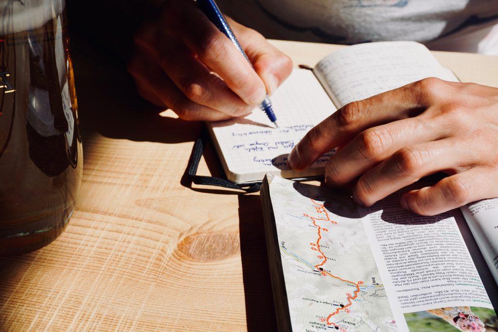 Jemand schreibt Tagebuch – Nahaufnahme mit Hand und Buch.