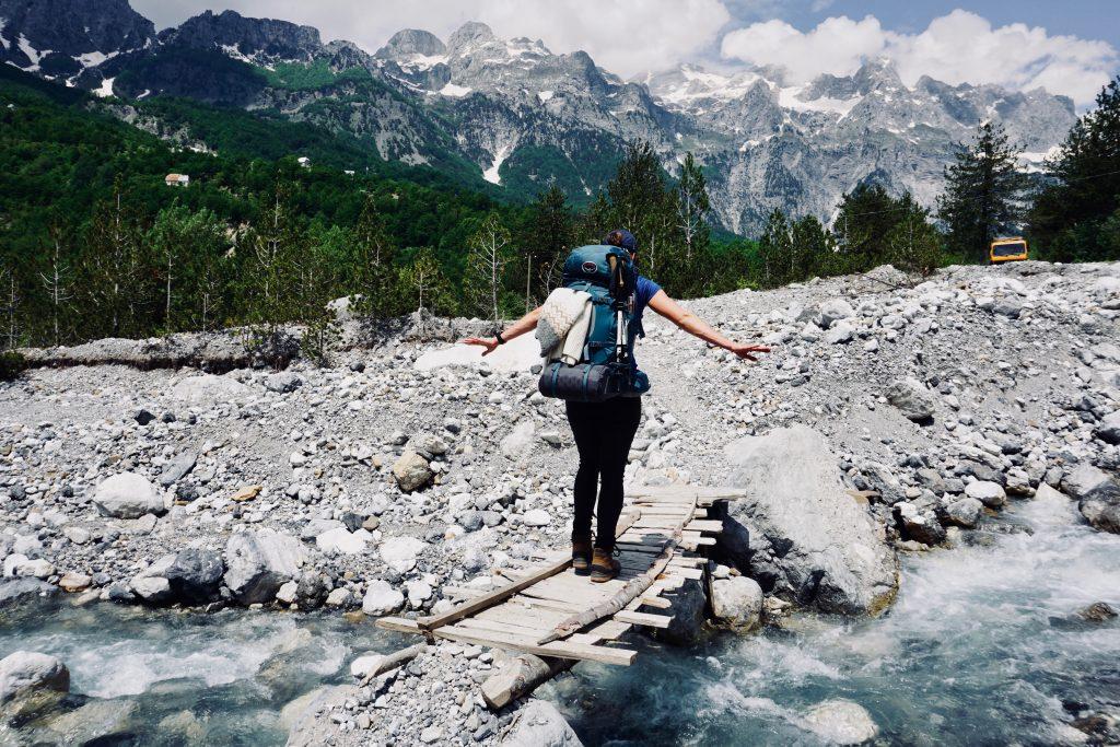Eine Frau mit Trekkingrucksack balanciert auf einer kleinen Holzbrücke über einen Bach auf dem Peaks of the Balkans Trail.