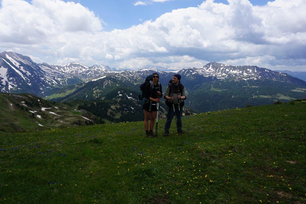 Torsten und Anna stehen auf einer grünen Wiese mit Gebirgsaussicht auf dem Peaks of the Balkans.