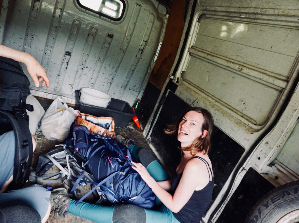 Eine Frau sitzt mit Rucksack auf der Ladefläche eines Transporters während ihrer Reise auf dem Peaks of the Balkans.