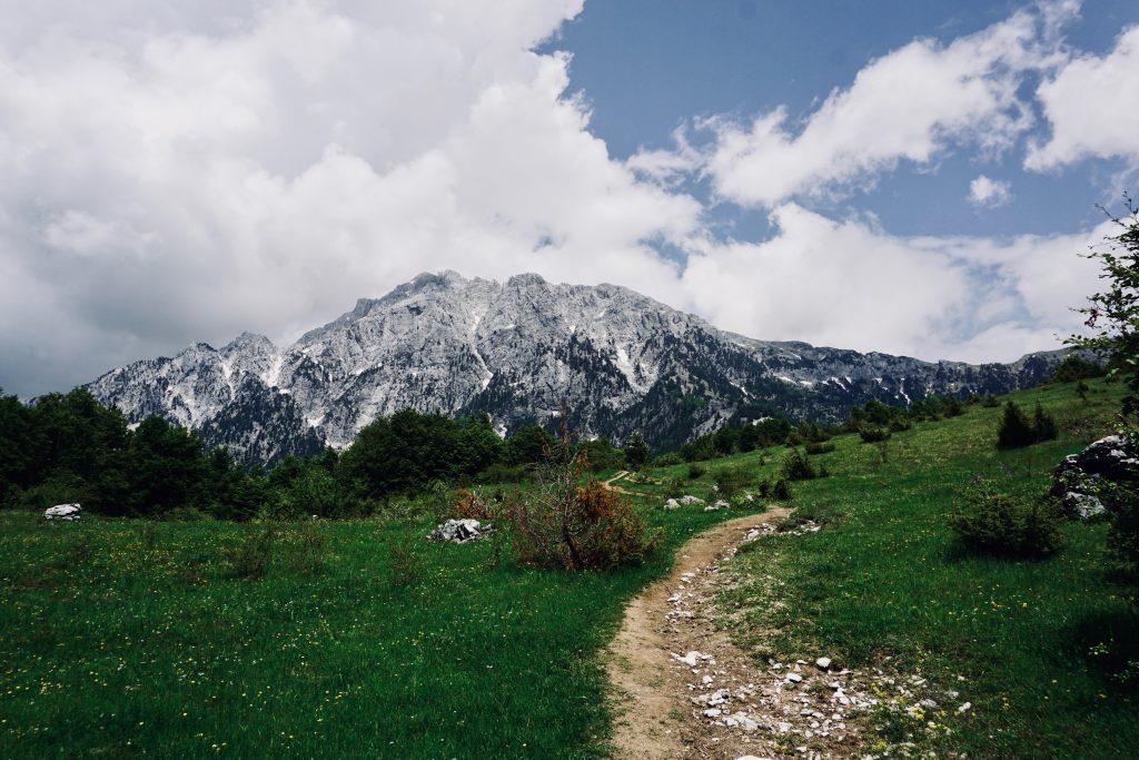 Ein erdiger Pfad inmitten einer grünen Wiese führt auf dem Peaks of the Balkans auf einen Berg am Horizont zu.