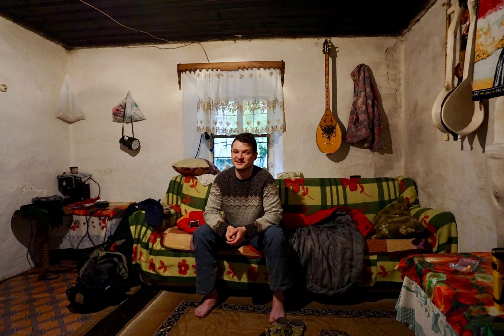 In einer urigen Hütte mit Holzinstrumenten an den Wänden, Teppichen und niedriger Decke.